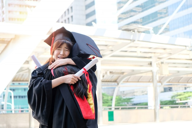 Duas lindas garotas asiáticas abraçam a cerimônia de formatura
