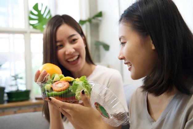 Duas lindas garotas asiáticas estão em dieta, comendo salada.