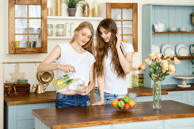 Duas lindas garotas bebendo limonada e conversando na cozinha
