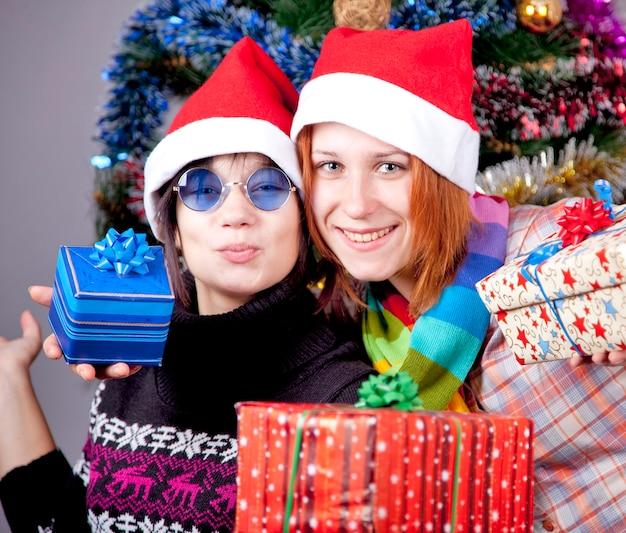 Duas lindas garotas com presentes em chapéus de natal perto de árvore de natal.