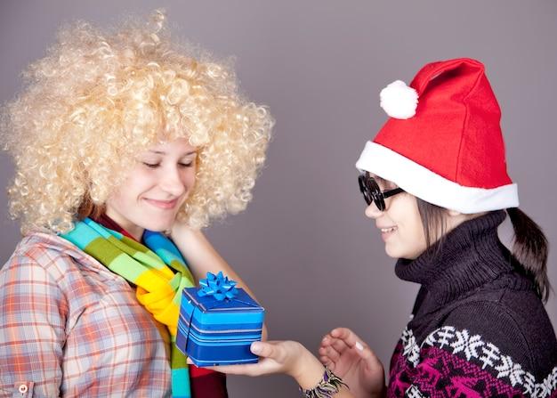 Duas lindas garotas com presentes em chapéus de natal. tiro do estúdio.