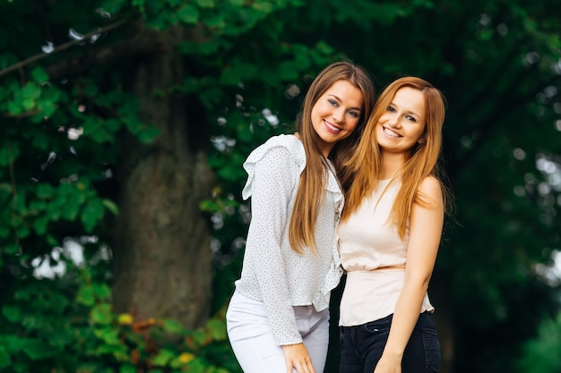 Duas lindas garotas com roupas elegantes olham para a câmera e sorriem no fundo do parque
