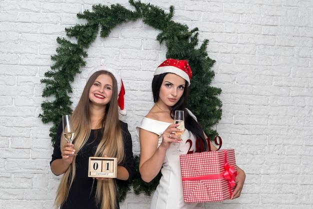 Duas lindas garotas comemorando ano novo com champanhe