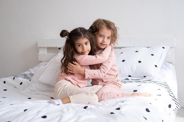 Duas lindas garotas diversificadas de pijama se abraçando na cama em um apartamento moderno e bem iluminado