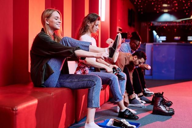 Duas lindas garotas e seus namorados trocando calçados antes de jogar boliche sentados no banco de um centro de lazer