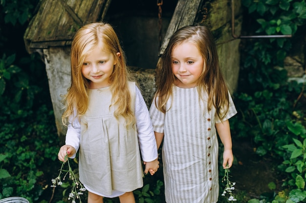 Duas lindas garotas em camisas antigas brancas perto de um poço em um fundo de grama e árvores
