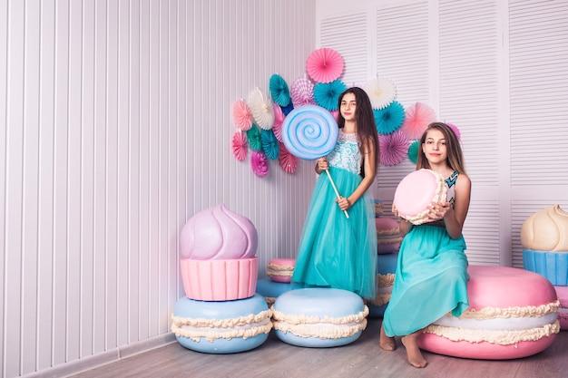 Duas lindas garotas em vestidos azuis seguram nas mãos enormes doces e biscoitos com decoração de macarons