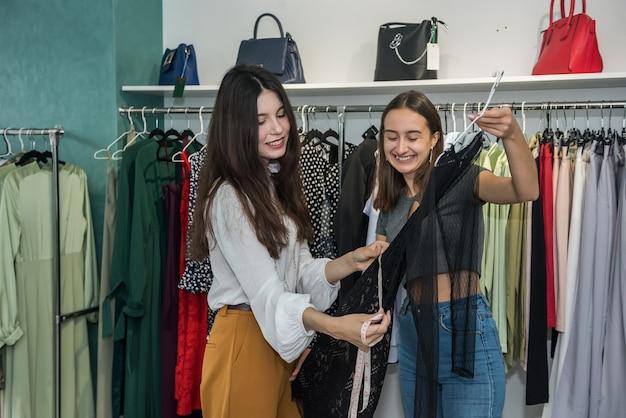 Duas lindas garotas escolhem roupas novas na loja de moda para comemorar. estilo de vida