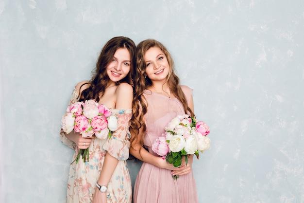 Duas lindas garotas estão em um estúdio e seguram buquês de flores.