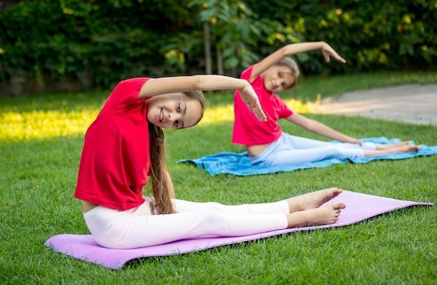 Duas lindas garotas fazendo alongamento e fazendo ioga no parque