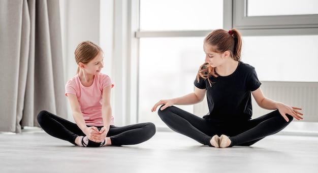 Duas lindas garotas fazendo alongamento nas pernas, sentadas no chão em posição de borboleta durante a aula de coreografia de balé
