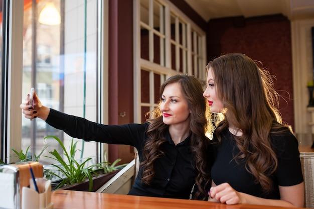 Duas lindas garotas fazendo selfi e tomando café