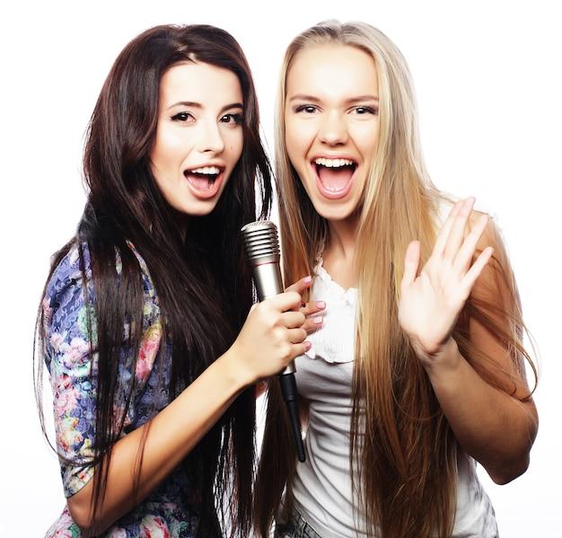 Duas lindas garotas hippie com um microfone cantando e se divertindo
