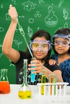Duas lindas garotas indianas ou asiáticas experimentando ou estudando ciências em laboratório, sobre fundo de quadro verde com rabiscos educacionais