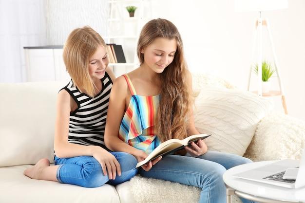Duas lindas garotas lendo livro no sofá