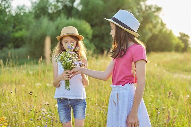 Duas lindas garotas lindas crianças rasgando flores silvestres, caminhando num prado ensolarado, paisagem pitoresca, hora dourada. infância, verão, natureza, beleza, conceito infantil