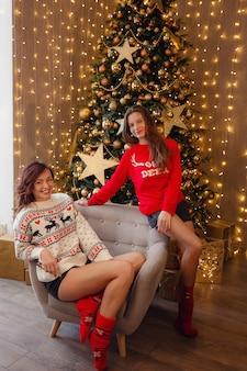 Duas lindas garotas na véspera de ano novo. melhores amigas da jovem comemorando o natal em casa. prazer amizade nunca termina o conceito. lindas decorações douradas de natal em uma alta árvore de natal