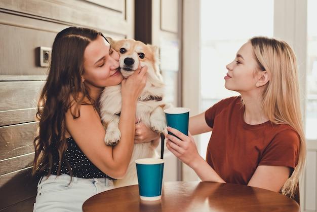 Duas lindas garotas passam um tempo em um café com um cachorro da raça corgi