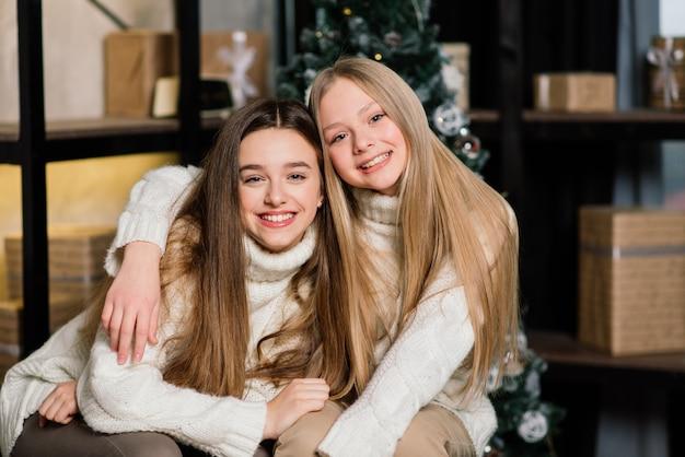 Duas lindas garotas posando com beijo de expressão facial na festa de aniversário. mulher europeia de cabelos compridos ao lado de uma árvore e presentes