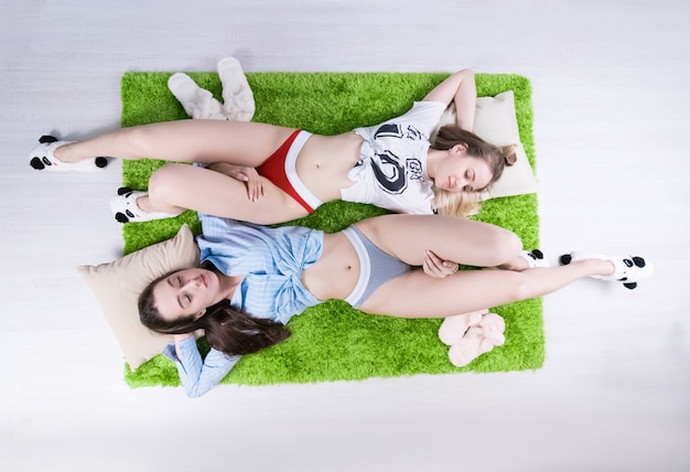 Duas lindas garotas sensuais deitadas em um tapete verde (foto acima) com calcinhas elegantes, ao lado de chinelos de hera (relacionamento do mesmo sexo)