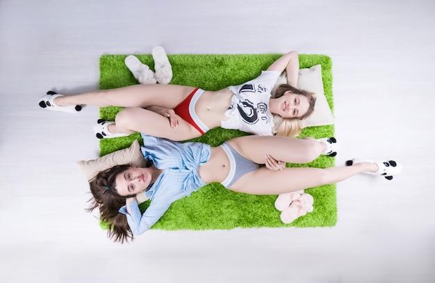 Duas lindas garotas sensuais deitam-se em um tapete verde (foto acima) com calcinhas elegantes, ao lado de chinelos de hera (relacionamento do mesmo sexo)