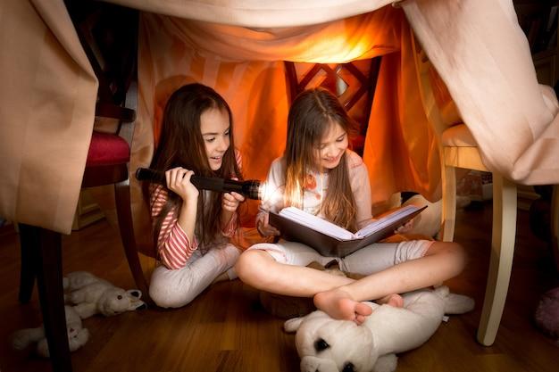 Duas lindas garotas sentadas embaixo de cobertores lendo um livro com uma lanterna
