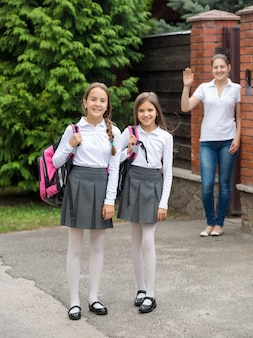Duas lindas garotas sorridentes saindo de casa para a escola pela manhã
