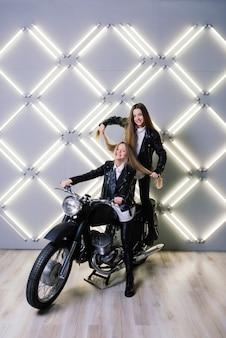 Duas lindas garotas vestindo fantasias de pilotos e sentadas em uma motocicleta, no estúdio