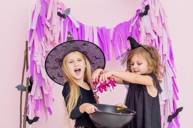 Duas lindas garotinhas fofas em fantasias de bruxa de carnaval na moda do halloween