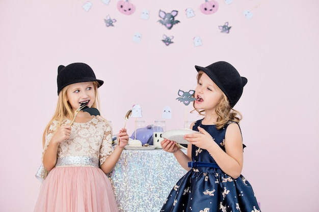 Duas lindas garotinhas fofas em fantasias de carnaval em uma mesa com decorações de halloween