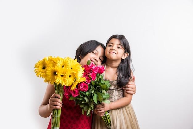 Duas lindas garotinhas indianas segurando um ramo ou buquê de rosas vermelhas frescas ou flores de gulab. isolado sobre fundo branco
