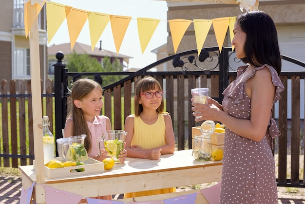 Duas lindas garotinhas paradas perto da barraca de madeira, olhando para uma jovem e linda mulher em um vestido elegante tomando um copo de limonada caseira fresca