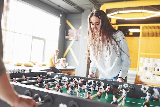 Duas lindas gêmeas jogam futebol de mesa e se divertem.