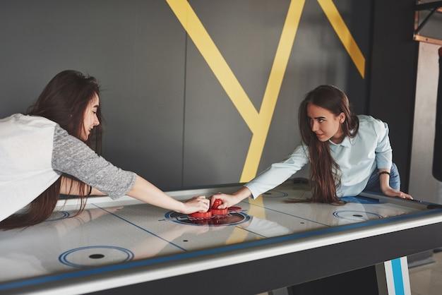 Duas lindas gêmeas jogam hóquei no ar na sala de jogos e se divertem.