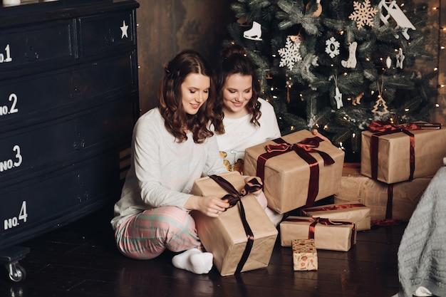 Duas lindas irmãs, amigas ou primas embrulhando e decorando lindos presentes de natal sentadas no chão