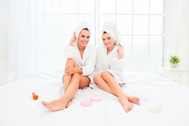 Duas lindas irmãs em roupões de banho com pernas macias sentadas na cama