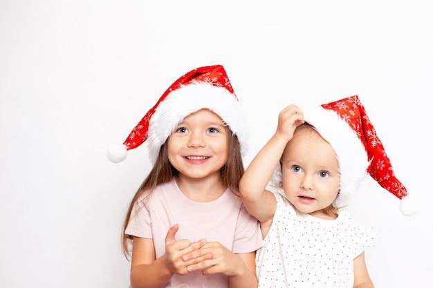 Duas lindas irmãs europeias em bonés de natal em um fundo branco ano novo de 2022