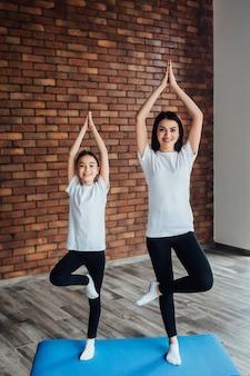 Duas lindas irmãs fazendo exercícios matinais com tapete de ioga azul.