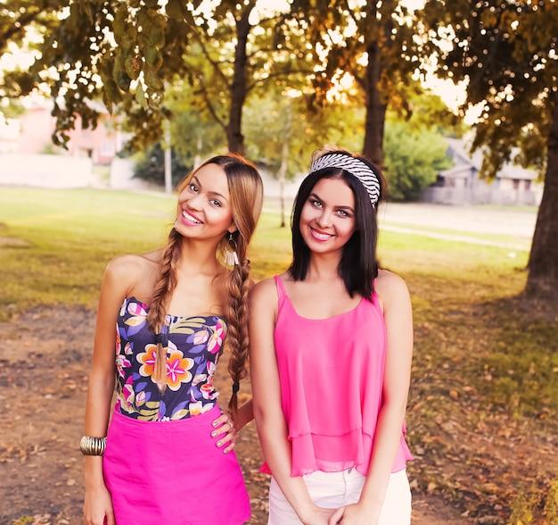 Duas lindas irmãs garotas hipster se abraçando e se divertindo juntas