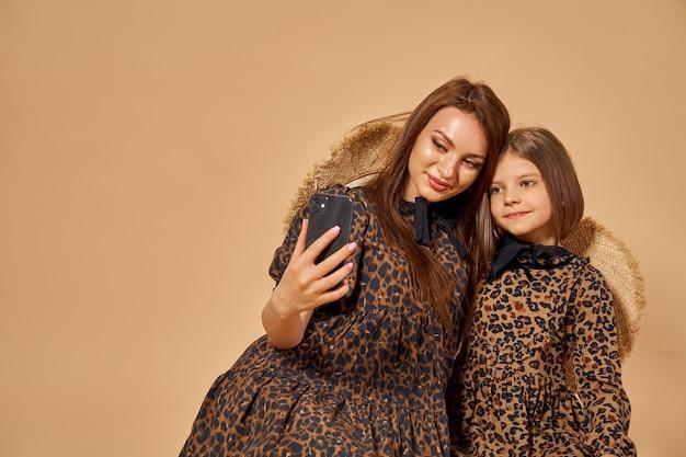 Duas lindas irmãs jovens tirando selfies em lindos vestidos de estampa animal com chapéus de palha