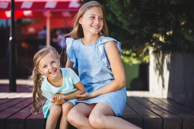 Duas lindas irmãs sentadas fazendo cócegas e rindo no parque