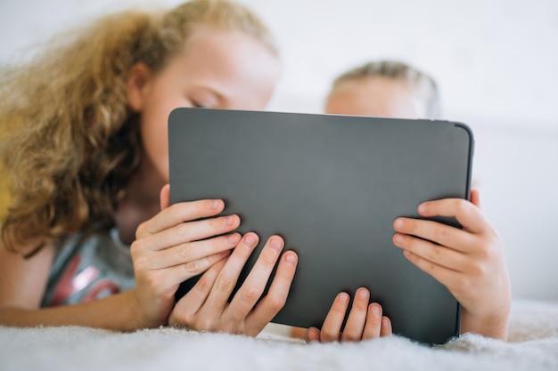 Duas lindas irmãzinhas deitada na cama e olhem para a tela de um tablet, crianças inteligentes usando tecnologia inteligente