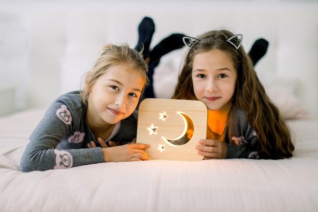 Duas lindas irmãzinhas, deitada na cama em casa e curtindo seu tempo brincando com a lamparina de madeira com imagens de lua e estrelas.