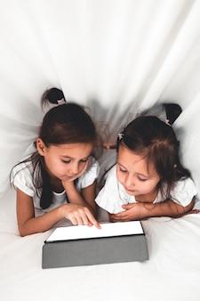 Duas lindas irmãzinhas deitadas na cama olhando para a tela de um tablet, crianças inteligentes usando tecnologia inteligente