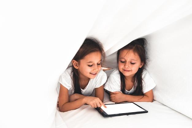Duas lindas irmãzinhas deitadas na cama olhando para a tela de um tablet