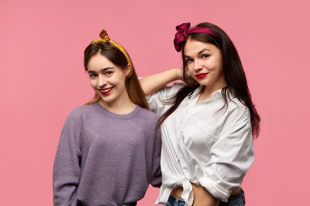 Duas lindas jovens amigas europeias elegantes, vestindo roupas elegantes e brilhantes, fazem-se passar um bom tempo juntas, olhando para a câmera com expressões faciais alegres e alegres, sorrindo