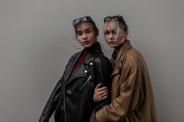 Duas lindas jovens irmãs na moda com roupas da moda em pé perto de uma parede cinza na cidade