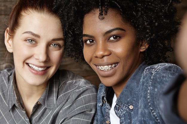 Duas lindas lésbicas felizes relaxando em um café, tendo expressões faciais alegres e alegres