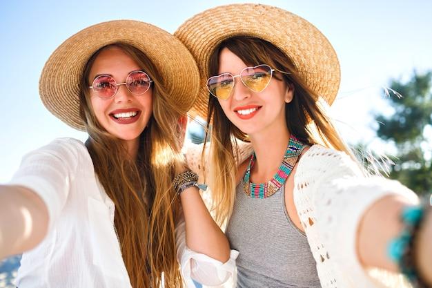 Duas lindas melhores amigas fazendo selfie na praia, cores claras e brilhantes do verão, chapéus e óculos de sol com roupas chiques boho, joias da moda e maquiagem natural, vibrações positivas de amizade.