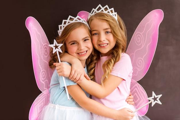 Duas lindas meninas abraçando e sorrindo.